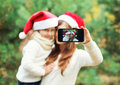 Christmas and technology concept - mother and child taking picture self portrait on smartphone together Royalty Free Stock Photo
