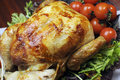 Christmas or thanksgiving roast chicken turkey close up platter of delicious with salad greens and red tomatoes on the vine for a Royalty Free Stock Photography