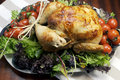 Christmas or thanksgiving roast chicken turkey dinner platter of delicious with salad greens and red tomatoes on the vine for a Royalty Free Stock Photos