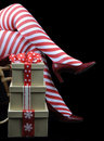 Christmas theme lady santa with red and white candy cane stripe stocking legs and gifts merry on black background Stock Images