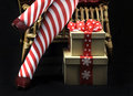 Christmas theme lady santa with red and white candy cane stripe stocking legs and gifts merry on black background Royalty Free Stock Photo