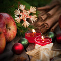 Christmas time candles with several spices and apples Stock Photos