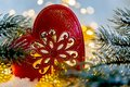 Christmas toy red heart with ornament on the snow. Greeting card Happy New Year and Merry Christmas. Beautiful bokeh. Macro.