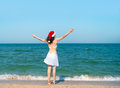 Christmas travel young girl in santa s hat pulls her hands to the sky Royalty Free Stock Photo