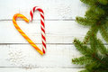 Christmas treats: bright candy canes, in a heart shape and green spruce branches on white a wooden board. Royalty Free Stock Photo