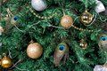 Christmas tree with baubles, peacock feather, garlands Royalty Free Stock Photo