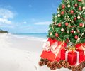 Christmas tree the beach and gifts over background Royalty Free Stock Photos