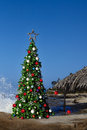Christmas tree on beautiful tropical beach thatched palm palapa house decorated with ornaments lights holiday background Royalty Free Stock Photos