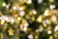 Christmas tree bokeh light in green yellow golden color, holiday abstract background, blur defocused Royalty Free Stock Photo