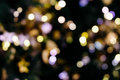 Christmas tree bokeh light in green yellow golden color, holiday abstract background, blur defocused with grain hipster color. Royalty Free Stock Photo