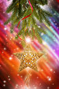 Christmas tree branch with star a pine from a a golden hanging downward the background is a brightly colored blur stars and Stock Images