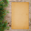 Christmas tree branches and old paper on wooden background Stock Image