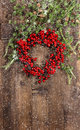 Christmas tree branches and wreath from red berries green over rustic wooden background festive decoration with snowflakes effect Royalty Free Stock Images