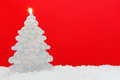Christmas tree candle red background shaped on snow against a Royalty Free Stock Photo