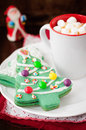 Christmas tree cookies on a white plate with a cup of coffee or hot chocolate topped marshmallow Royalty Free Stock Photo