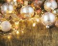 Christmas tree decoration glass balls and light garland over rustic wooden background