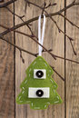 Christmas tree decoration hanging on a twig against wooden background Royalty Free Stock Image