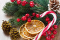 Christmas tree decorations with dried orange slices holly berries and candy on wooden background Stock Photos