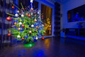 Christmas tree with decorations at home in the dark living room Royalty Free Stock Photo