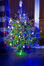Christmas tree with decorations at home in the dark living room Royalty Free Stock Photography
