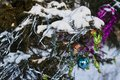 Christmas tree in the forest decorated with sweets and a garland and a blue ball and branches of fir covered with snow. Royalty Free Stock Photo