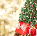 Christmas tree and gifts over golden sparkle background Royalty Free Stock Images
