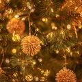 Christmas tree with gold bauble ornaments. Decorated Christmas tree closeup. Balls and illuminated garland with Royalty Free Stock Photo