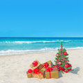 Christmas tree and golden gift boxes with big red bow on the sea sandy beach vacation concept Stock Photography