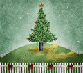 Christmas tree a on a grassy hill enclosed by a white picket fence Stock Photo