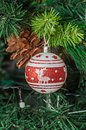 Christmas tree hanging ornament, red globe with reindeer, close Royalty Free Stock Photo