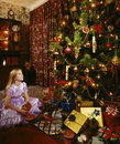 Christmas tree and little girl a in a party dress with a pile of gifts a large Stock Photo