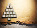 Christmas tree made of computer keys and feather, Old paper background Royalty Free Stock Photo