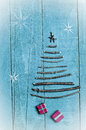 Christmas tree made from dry sticks on wooden, blue background. Snow flaks image. Christmas tree ornament, craft, gifts
