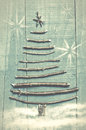 Christmas tree made from dry sticks on wooden, blue background.