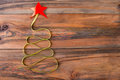 Christmas tree made of green ribbon with a red star on the wooden background.