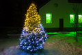 Christmas tree night with lights and rural house Royalty Free Stock Photography