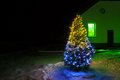 Christmas tree night with lights and rural house Royalty Free Stock Photo