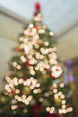 Christmas tree perspective defocused with bokeh lights tall decoration ornaments ribbons poinsettia and presents under the Royalty Free Stock Photos