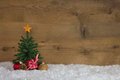 Christmas tree with presents on a wooden background with snow. Royalty Free Stock Photo