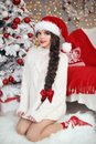 Christmas tree. Pretty teen girl in santa hat and white knitted Royalty Free Stock Photo