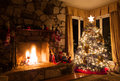 Christmas tree sits next to roaring fire rustic fireplace Stock Images