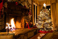 Christmas tree sits next to roaring fire rustic fireplace Royalty Free Stock Photography
