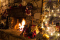 Christmas tree sits next to roaring fire rustic fireplace Royalty Free Stock Images