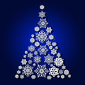Christmas tree from snowflakes, casts a shadow on blue