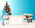 Christmas tree with snowman and postcard on blue background Royalty Free Stock Photos