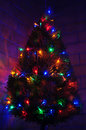 Christmas tree and wall with colorful lights with brick background Royalty Free Stock Photos