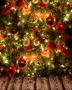 Christmas tree and wooden texture elegant decorated with baubles fairy lights it shines the lights dispelling the darkness of the Stock Image