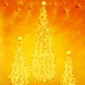 Christmas trees on yellow and orange background illuminated Royalty Free Stock Images