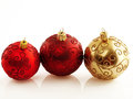 Christmas trio three holiday baubles in red and gold with soft reflection and copy space Stock Image