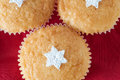 Christmas vanilla cupcakes overhead three on a red napkin background shot close up and decorated for with star shapes sprinkled in Royalty Free Stock Photos